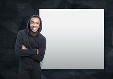 Smiling African man near a blank poster. Portrait of a smiling African American young man wearing a black hoodie and standing with crossed arms near a blank stock image