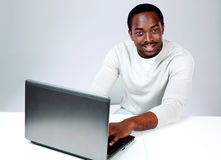 Smiling african man sitting at the table Stock Photography