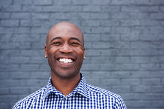 Smiling african man standing against a gray wall. Close up portrait of smiling african man standing against a gray wall Royalty Free Stock Image