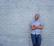 Smiling african man standing with his arms crossed. Portrait of smiling african man standing with his arms crossed against gray background Royalty Free Stock Photo