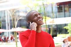 Smiling african man standing on street talking on mobile. Portrait of smiling african man standing on street talking on mobile Stock Photography