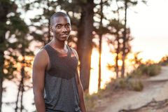 Smiling African man standing on a trail while out jogging Royalty Free Stock Image