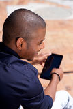 Smiling african man using digital tablet outside Stock Photography