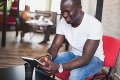 Smiling African man using tablet for video conversation in modern office. Concept of young business people working at home Royalty Free Stock Photos