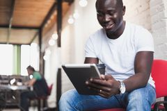 Smiling African man using tablet for video conversation in modern office. Stock Photography