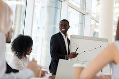Smiling african mentor giving presentation at office training. Smiling friendly african american businessman mentor giving presentation at diverse team office stock photos