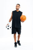 Smiling african sports man holding basketball and soccer ball Royalty Free Stock Image