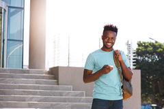 Smiling african student holding cellphone and bag on campus. Portrait of smiling african student holding cellphone and bag on campus Stock Image
