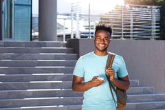 Smiling african student walking by stairs with bag and smart phone. Portrait of smiling african student walking by stairs with bag and smart phone Royalty Free Stock Photo