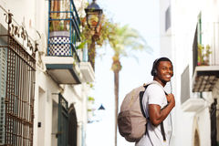 Smiling african travel man with bag listening to music Stock Photo