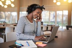 Smiling African university student listening to music between cl. Smiling young African college student sitting on campus working online with a laptop and royalty free stock photo