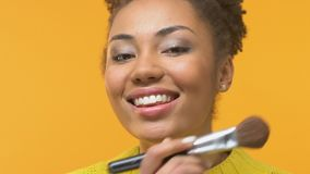 Smiling african woman applying blush by make-up brush, beauty trends, fashion. Stock footage stock video footage