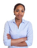 Smiling african woman in a blue shirt with crossed arms Stock Image