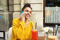 Smiling african woman at coffeeshop making phone call Royalty Free Stock Photos