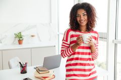 Smiling african woman drinking coffee and looking at the camera. While standing near the table on the kitchen Stock Photos