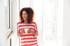 Smiling african woman drinking coffee. And looking at the window Royalty Free Stock Images