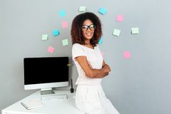 Smiling african woman in eyeglasses standing near the table Royalty Free Stock Image