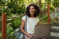 Smiling african woman in forest with laptop. Computer looking away Royalty Free Stock Images