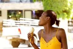 Smiling african woman holding ice cream cone outside Royalty Free Stock Photography