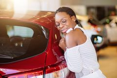 Smiling african woman hugging red car at new car showroom. Smiling african woman hugging a red car at new car showroom Stock Image