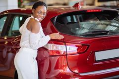 Smiling african woman hugging red car at new car showroom. Smiling african woman hugging a red car at new car showroom Royalty Free Stock Image