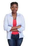 Smiling african woman with jeans and crossed arms Stock Photos