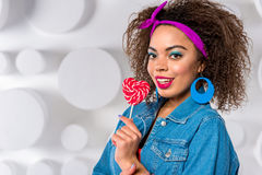 Smiling african woman keeping lollipop royalty free stock photography