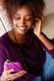Smiling african woman  listening to music with smart phone Royalty Free Stock Photography