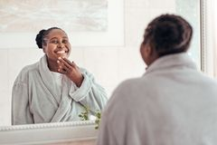 Smiling African woman looking in her bathroom mirror. Smiling young African woman wearing a robe looking at her complexion in the mirror while standing in her Stock Image