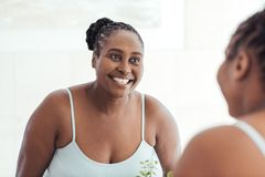 Smiling African woman looking at her reflection in a mirror. Smiling young African woman looking at her complexion in the mirror while standing in her bathroom Royalty Free Stock Photography