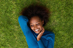 Smiling african woman lying on grass Royalty Free Stock Images