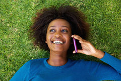 Smiling african woman lying on grass talking on mobile phone Stock Image