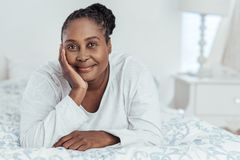 Smiling African woman lying on her bed in the morning royalty free stock images
