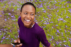 Smiling african woman outdoors holding mobile phone. Close up portrait of smiling young african woman relaxing outdoors holding a mobile phone and looking away Royalty Free Stock Photo
