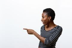 Smiling African woman pointing to the side. Towards blank copy space on a white background in an upper body profile view Stock Photo