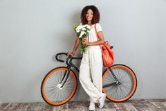 Smiling african woman posing with bicycle, backpack and flowers Stock Photography