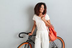 Smiling african woman posing with bicycle and backpack Royalty Free Stock Photography