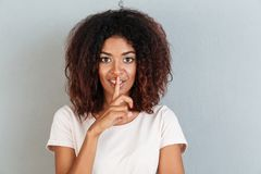 Smiling african woman showing silence gesture. With finger on her lips isolated over white background Stock Image