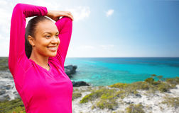 Smiling african woman stretching hand on beach Royalty Free Stock Images