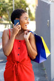 Smiling african woman talking on cell phone with shopping bags Stock Photos