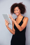 Smiling african woman using tablet computer Royalty Free Stock Images