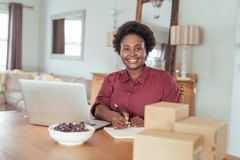 Smiling African woman working on her home based business Royalty Free Stock Image