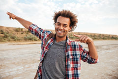 Smiling african young man pointing away by both hands outdoors Royalty Free Stock Photo