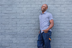 Smiling afro american man leaning against gray wall Royalty Free Stock Photos