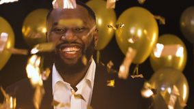 Smiling Afro-American man standing under falling confetti, party decorations. Stock footage stock video