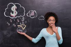 Smiling afro-american woman with dollar signs and Stock Photo