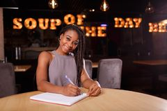 A smiling Afro-American woman is working stock photos