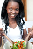 Smiling Afro-american woman preparing a salad Royalty Free Stock Image