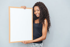 Smiling afro american woman showing blank board Royalty Free Stock Photography
