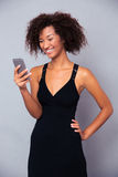 Smiling afro american woman using smartphone Stock Photos